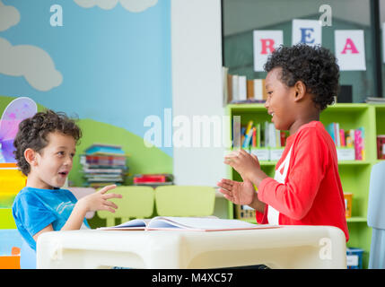 Two boy kid sit on table and coloring in book  in preschool library,Kindergarten school education concept. - Stock Photo