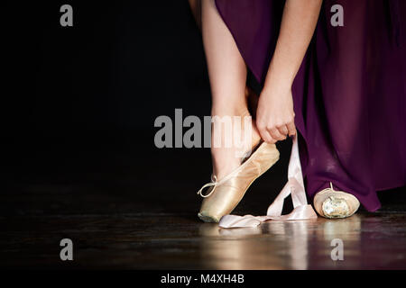 Young Ballerina getting ready for a classical dance. Girl wearing point shoes, tigheting a silk ribbon around her - Stock Photo
