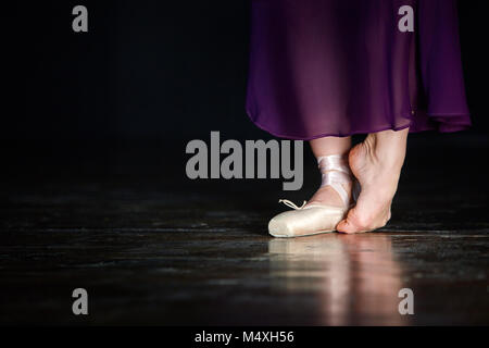 Elegant ballerina is posing in the studio on the dark background. She stands on the left toe and holds right leg - Stock Photo