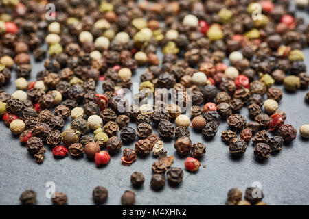 mixture of pepper peas powder scattered on a slate plate. Closeup - Stock Photo