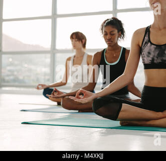 Women meditating while sitting in fitness studio. Young woman practicing yoga in gym class with females sitting - Stock Photo