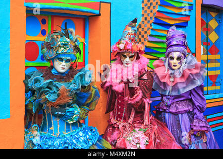 Three costumed ladies in front of a colorful house during the Carnival of Venice (Carnevale di Venezia) in Burano, - Stock Photo