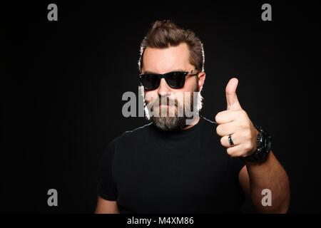 A handsome, strong man with a stylish hairstyle and beard shows thumb up in the Studio on a black background. With - Stock Photo