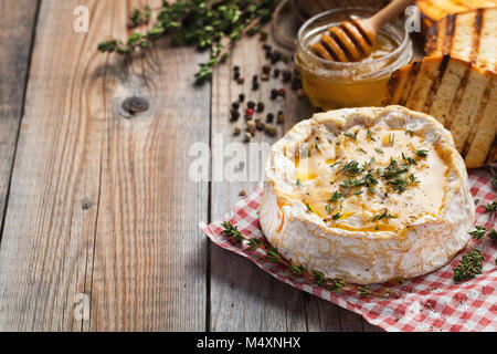 A real Camembert from France with thyme, honey and toasted bread on old wooden rustic table. Soft cheese on a wooden - Stock Photo