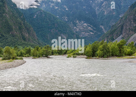 A fast mountain river flowing in the valley between the mountains, with forest and clouds on the slopes - Stock Photo