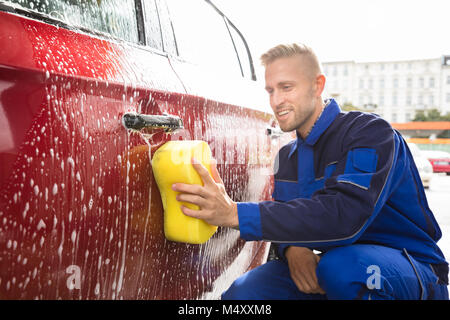 Close-up Of Worker's Hand Washing Red Car With Yellow Sponge At Service Station - Stock Photo