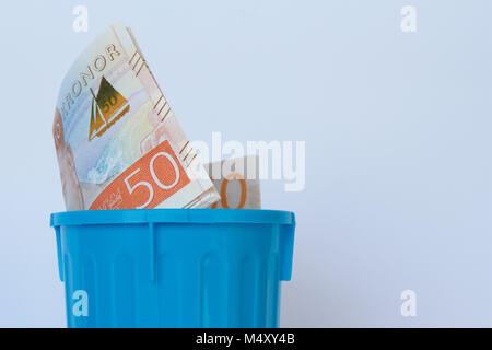Fifty Swedish kronor notes in a blue garbage bin. - Stock Photo