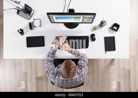 High Angle View Of A Male Designer Holding Color Swatches And Using Computer In Office - Stock Photo