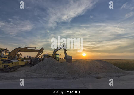 excavators in construction site at stunning sunset - Stock Photo