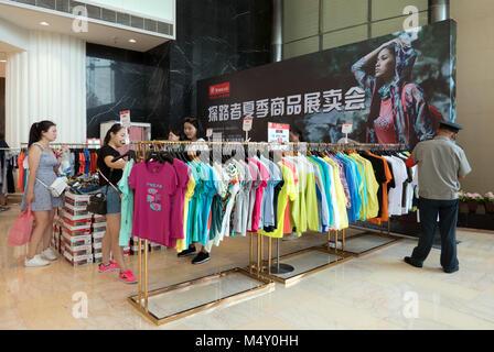 Buyers in mall in Tianfu square, Chengdu, Sichuan, China, Asia. Women choosing and buying clothes in Chinese shopping - Stock Photo