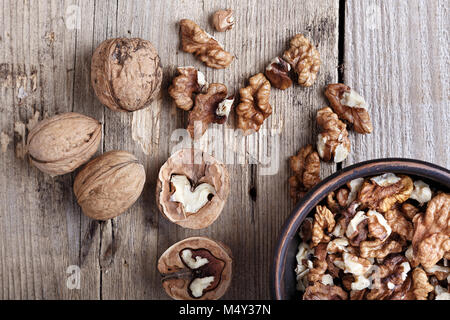 walnuts in a clay plate on a wooden background. top view - Stock Photo