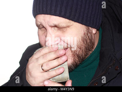 A bearded man in a blue down jacket and a knitted hat coughs, covering his mouth with a handkerchief - Stock Photo
