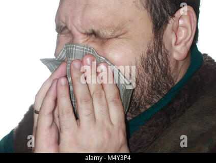 The sick man with the sneezes in a handkerchief - Stock Photo