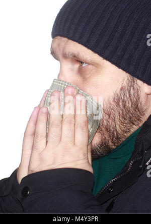 Sick bearded man blowing his nose in a handkerchief - Stock Photo
