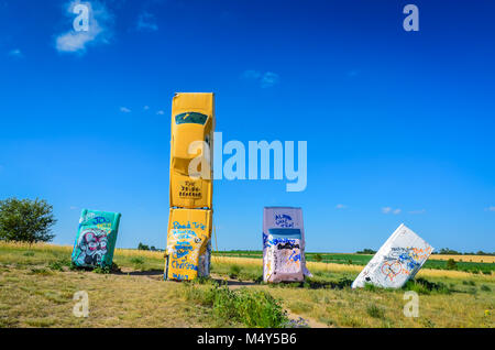 Outdoor sculpture of painted cars, arranged to look like Stonehenge, in a Nebraska field. This is a popular roadside - Stock Photo