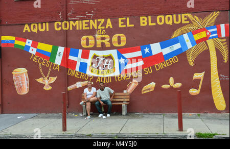Hispanic couple sits on bench in front of Golden Block Mural in Philadelphia, PA, USA. - Stock Photo