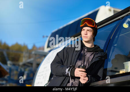 Portrait of modern young man wearing snowboarding gear relaxing leaning on truck and warming up with coffee, copy - Stock Photo