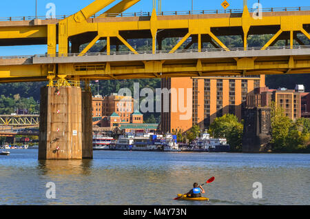 A lone man rows a kayak on the Ohio River under a yellow bridge in Pittsburgh, Pennsylvania. - Stock Photo