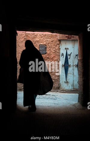 A dark silhouette of a Moroccan woman in traditional dress against a light coloured stone wall. The wall is peach - Stock Photo