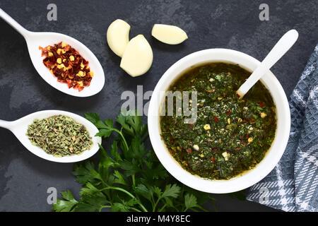 Raw homemade Argentinian green Chimichurri or Chimmichurri salsa or sauce made of parsley, garlic, oregano, hot - Stock Photo