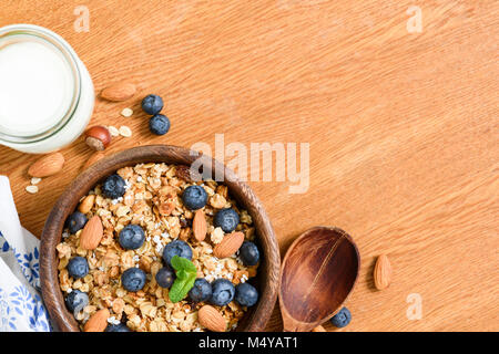 Granola with nuts and berries, milk on wooden table. Top view with copy space for text. Concept of weight loss diet, - Stock Photo
