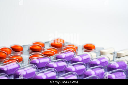 Macro shot detail of orange, purple and white tablets pills in blister pack on white background. Colorful medicine - Stock Photo