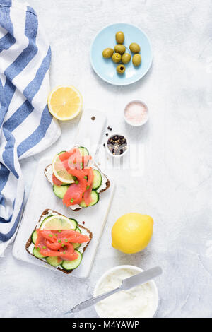 Sandwiches with salmon, cucumber and cream cheese on white background. Top view. Mediterranean cuisine - Stock Photo