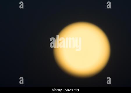 Golden glow of full moon against black night sky. - Stock Photo
