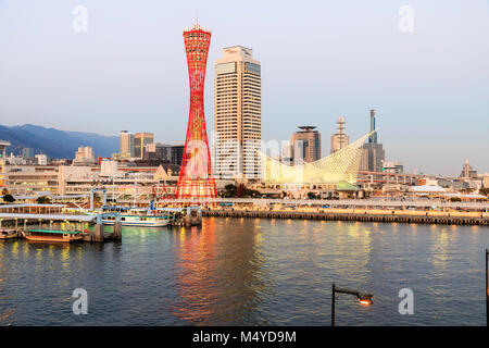 Japan, Kobe. Red Kobe Port Tower, with Okura Hotel behind, and the maritime museum. Night time, twilight period. - Stock Photo