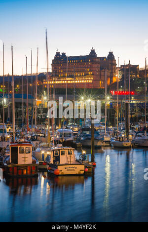 Scarborough harbour, view at dusk of the harbour area and, beyond, the Grand Hotel sited on the skyline of Scarborough, - Stock Photo