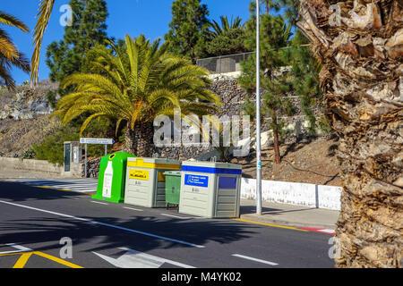 Waste recycling bins, palm trees, Guia de Isora, Tenerife, Spain - Stock Photo