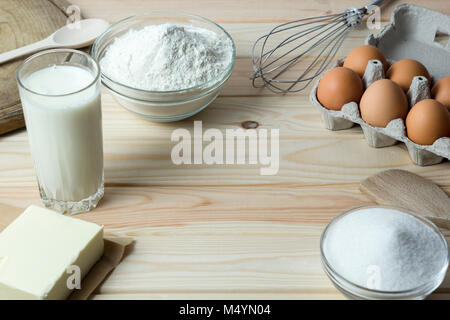 Ingredients for baking dough. Flour, eggs, butter, milk and sugar on the kitchen table. - Stock Photo