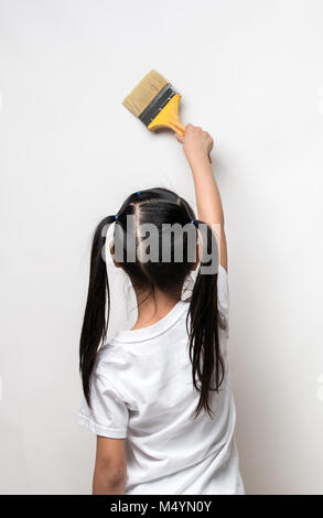 Little girl drawing something using painting brush on wall background - Stock Photo