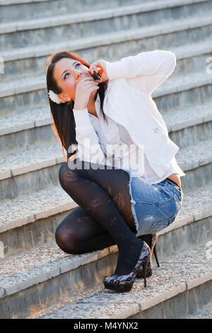 Young woman legs spike spiked heels in denims squatting looking up upwards away aside while feverishly talk talking on cellphone Stock Photo