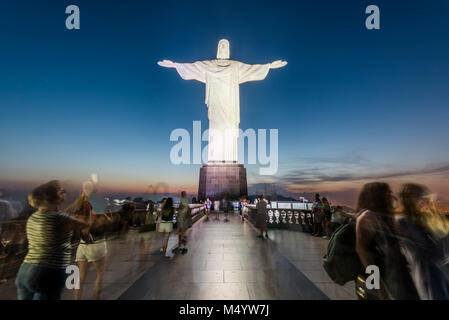 Christ the Redeemer statue with tourists at sunset, Corcovado Mountain, Rio de Janeiro, Brazil - Stock Photo
