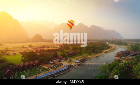 Aerial view by Drone : Hot air balloon over Nam Song river in Vang vieng, Laos on sunset - Stock Photo