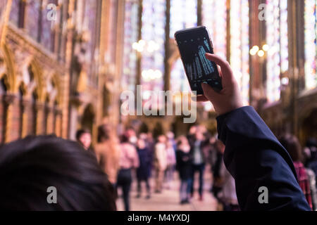 Woman taking photo of stained glass in Sainte-Chapelle, Paris, France - Stock Photo