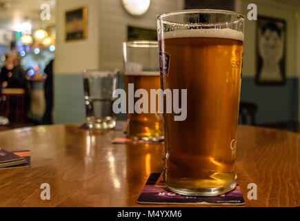 Real ale in a glass on a table top in a pub - Stock Photo