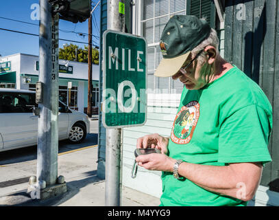 Geocacher checks GPS at beginning point of U.S. Route 1. US 1 travels along the east coast of Florida, beginning - Stock Photo