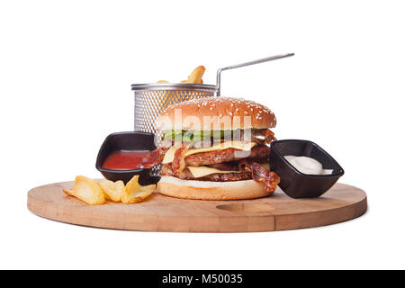 big double roasted hamburger on wooden plate with ketchup and mayonnaise in black pots  isolated over white background. - Stock Photo