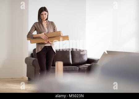 Young woman doing DIY repairs at home putting together self assembly furniture - Stock Photo