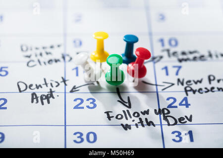 Colorful Pushpins Stuck On Calendar With Important Appointment Written On It - Stock Photo