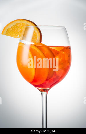 Trendy popular Italian drink Summer refreshing faintly alcoholic cocktail Aperol spritz in a glass glass with ice - Stock Photo