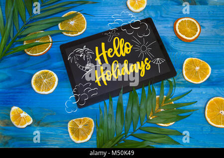 hello holidays concept with citrus fruits and palm leaves on blue wooden background - Stock Photo