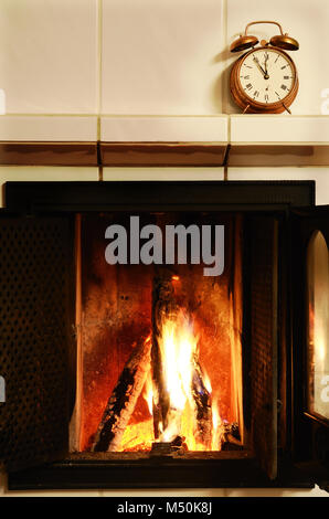 fireplace and  old-fashioned copper alarm clock on the mantelshelf - Stock Photo