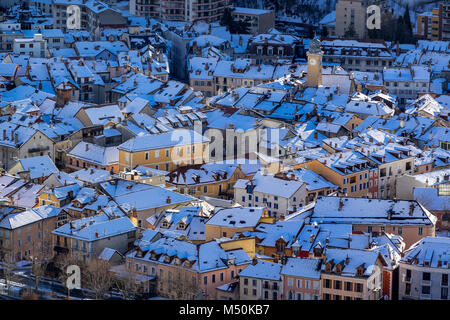Aerial Winter view of snow covered rooftops in the city of Gap. Hautes-Alpes, Alps, France - Stock Photo