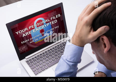 Worried Businessman Looking At Laptop With Ramsomware Word On The Screen At The Workplace - Stock Photo
