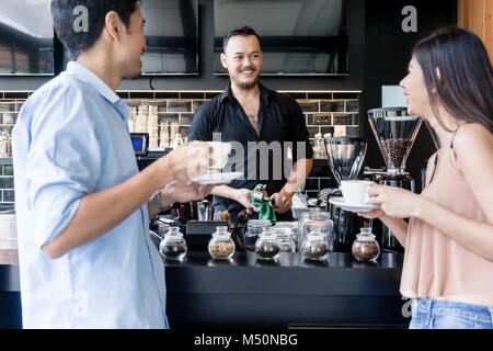 Cheerful young bartender cleaning the coffee maker while talking - Stock Photo