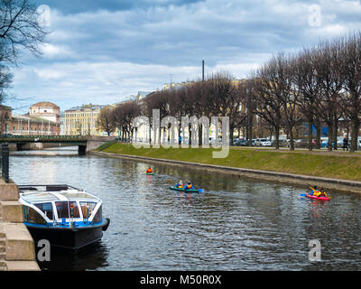 River Moika and a boat with canoe boats floating along the river in the center of the city of St. Petersburg in - Stock Photo