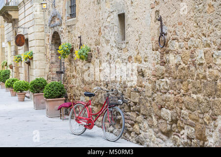 Red bicycle leaning against a wall - Stock Photo